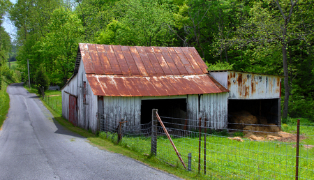 Barn sits right next to a narrow Tennesee country lane.  It is weathered and faded, wooden with a rusty tin roof.