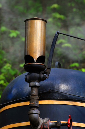 Blowing train whistle throws smoke into the air as train readies for a ride on the train tracks.  Whistle is bronze and train is black. Stockfoto