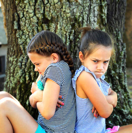 Two little girls sit back-to-back, outside besides a tree.  They both have their arms crossed and their expressions are angry.   Stock Photo