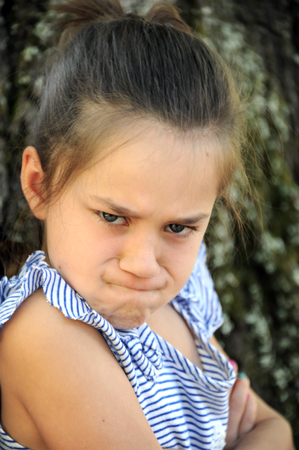 Closeup of this angry little girl, shows puckered brows, eyes shooting daggers, compressed mouth and angry folded arms.
