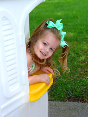 Little girl leans out of her white playhouse and invites everyone to come and play with her.  She has long blond curls and green ribbons.