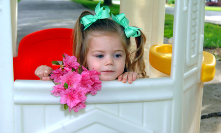 Little girl hangs dejectedly on the window of her playhouse. She is having to play all alone. Her hair is in pigtails and she is holding a bouquet of Azaleas. Stock Photo