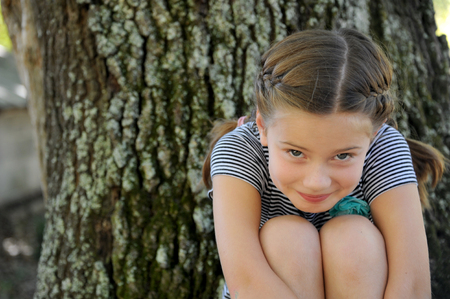 Pretty little girl hugs her knees and ducks her head.  Feeling teased she peeks up at the camera. Stock Photo