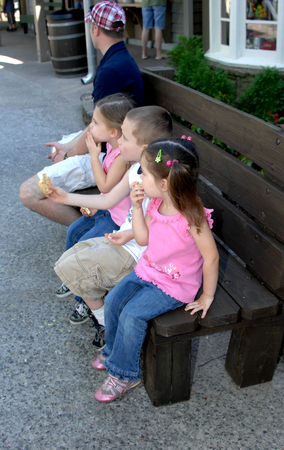 Family of four sit on a wooden bench. Father is looking away and the three children wait patiently to leave.
