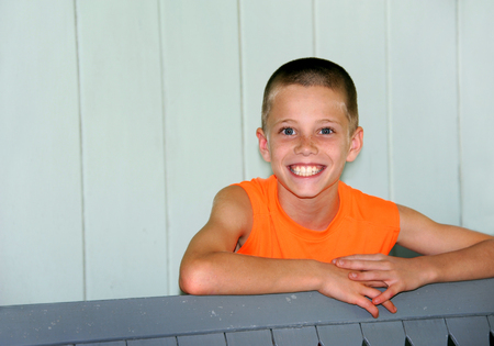 Little boy beams joy.  He has blone hair and a summer tan.  He is wearing a bright orange shirt and leaning on a wooden rail.