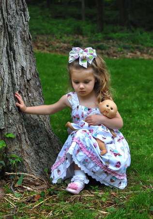 Little girl hugs her doll and kneels in the grass outdoors.  She is looking down lost in thought.  Her hand is against a tree.