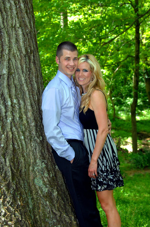 Young couple lean against a tree trunk and close to each other.  They are smiling and looking at the camera.  Both are wearing dressy clothes.
