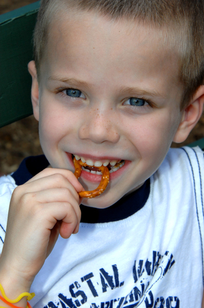 Little boy eats a pretzel while visiting a county fair.  He is smilng and his eyes are shining. Banco de Imagens