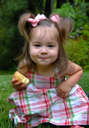 Little girl devours her half of an apple.  She is sitting on the grass in her yard and enjoying her healthy snack.  She has pigtails and ribbons.