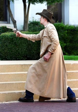 Period reenactor draws his gun in a shootout. He is wearing a long tan overcoat and a cowboy hat.