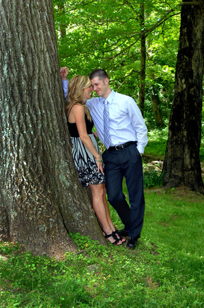 Woman laughs as man leans in close and rests his forehead against hers.  They are standing outside in a forest.  Happy laugh escapes woman as they share a secret. Imagens