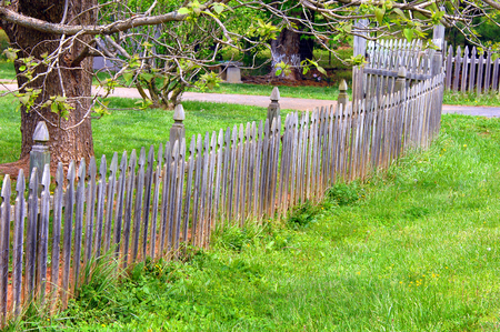 Long wooden fence curves to driveway.  Each slat of fence is pointed and decorative.  Fence is weathered, rustic and old.