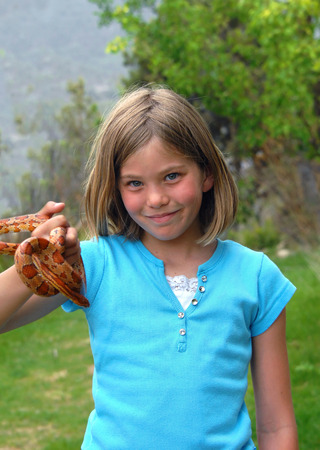 Little girl holds up her corn snake with pride.  They are both enjoying the outdoors.  Her smile holds pride in her pet.