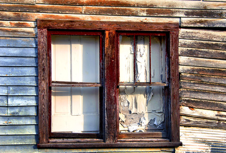 Wooden doors were used to board of the windows on this old house.  Window frame is cracked and peeled.  Portions of red paint remain.  Doors are peeling. Imagens