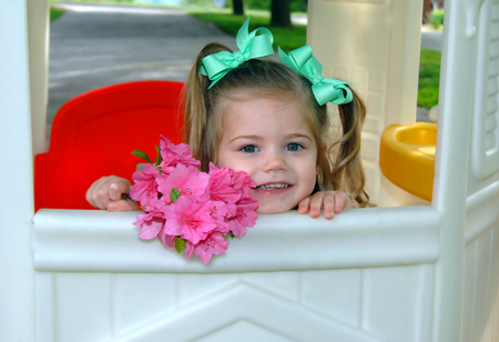 Little girl, holding a bouquet of pink azaleas, peeks out of her playhouse window.  She has pigtails and green ribbons.