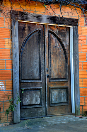 Creepy door looks haunted and ghostly.  It is weathered, cracked and overgrown.  Double doors have arch design and metal handle. 版權商用圖片