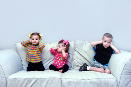 Three children sit on a couch in their home.  They are covering their ears and pretending to hear no evil.