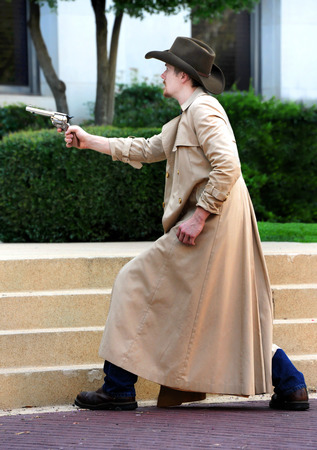 Periode reenactor trekt zijn pistool in een vuurgevecht. Hij draagt een lange bruine overjas en een cowboyhoed.