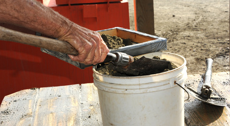 Man transfer his bucket of field dirt from the diamond field onto his screen for washing at the Crater of Diamonds State Parks' washing pavilion. Imagens