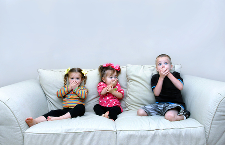 Three small children sit on a couch in their home, and cover their mouths with their hands.  They are pretending to speak no evil.