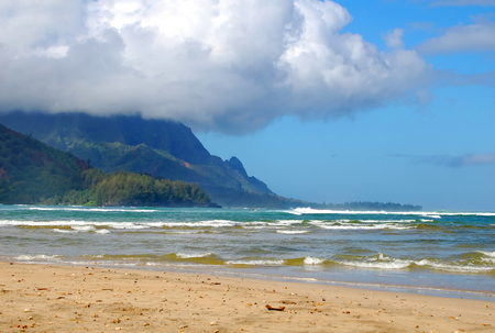 Turquoise waters surround the mountains in Hanalei Bay, Kauai, Hawaii.  Clouds expand and cover the mountain tops. 写真素材