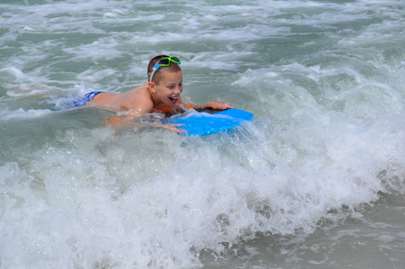 Young boy gleefully rides his first big wave on a boogie board at Madeira Beach, Florida.  His board is blue.