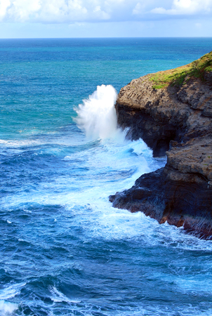 Large wave crashes against a cliff at Kilauea Point on the Island of Kauai, Hawaii.  Horizon is turquoise in the distance. Stock Photo