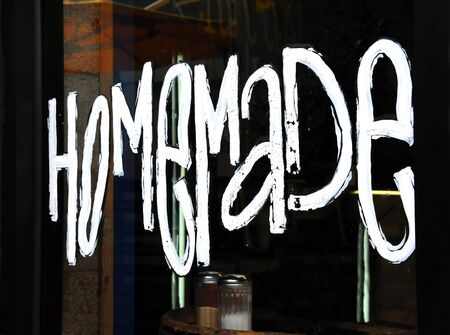 Hand painted sign states Homemade on exterior window of a cafe.  Suger dispensers can be seen through glass window.
