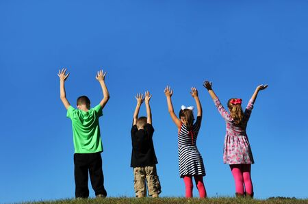 Four children raise their hands toward heaven and stand against a vivid blue sky.