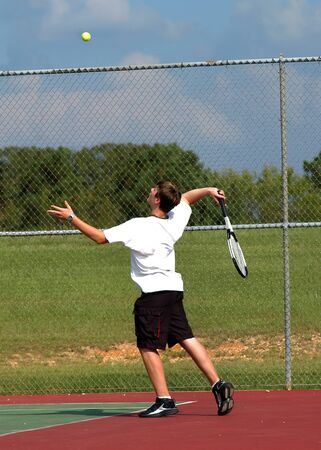Teenager throws tennis ball high in the air as he serves it.  He is keeping his eyes on the ball and his arm is in the motion of swining to serve. Фото со стока