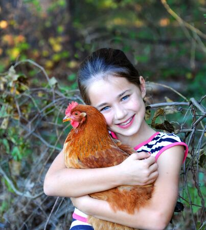 Beautiful little girl hugs her pet chicken.  She is smiling proudly and happily. Stock fotó