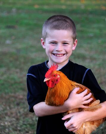 Little boy grins with happiness as he holds his prized, red chicken.  He has on a black shirt and pride is written all over his face.