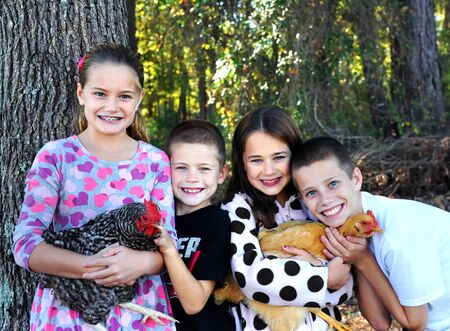 Four children cluster around their family pets, two chickens.  They are hugging them and petting them.  Smiles and pride cover childrens faces.