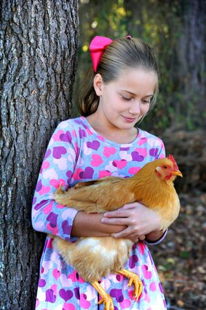 Young girl proudly holds her red, pet chicken.  She is looking down lovingly on her pet and leaning against a tree outdoors.