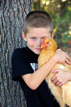 Young boy grins with happiness as he hugs his pet chicken.  The chicken used to the affection quietly stays still.