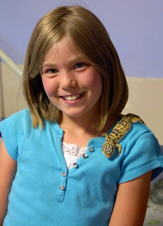 Child allows her pet Leopard Gecko to climb on her shoulder.  She is outdoors and is smiling.