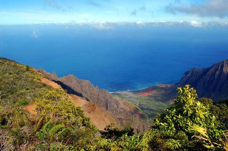 Beautiful aqua blue water hugs the Na Pali Coastline.  Kalalau Valley and Pali Mountains fill landscape on the island of Kaua, Hawaii.