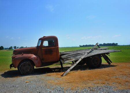 Old flat-bed farm truck sits rusting under the summer sun in Northwest Arkansas.  Tires are dry-rotted and flat.  Farm fields stretch behind truck.