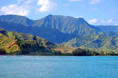 Beautiful Emerald Mountains hover over the turquoise waters of Hanalei Bay, on the island of Kauai, Hawaii. 스톡 콘텐츠 - 128873173