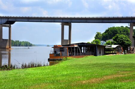 Houseboat sits rotting and abandoned on the bank of the Arkansas River. Steel bridge crosses the Arkansas River.