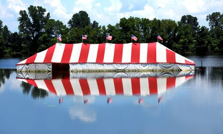 Mississippi River overflows low laying land and this fireworks stand ends up submerged.  Reflection of flooded tent shows in river water near Memphis, Tennessee. Imagens