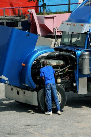 Diesel mechanic looks under the hood of an eighteen wheeler.  He has on jeans and a blue tee shirt. Reklamní fotografie