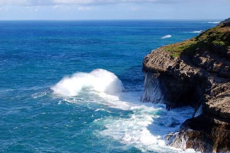 Waves rush to crash against the rugged cliffs at Kilauea Point Wildlife Sanctuary on the Island of Kauai. 스톡 콘텐츠 - 128872960