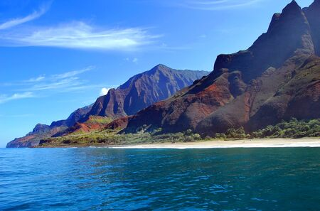 Small strip of beach, accessible only by boat, sits at the base of the rugged Na Pali Coast on the Island of Kauai, Hawaii. 스톡 콘텐츠 - 128872970