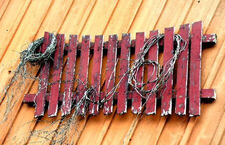 Abstract version of a rustic and weathered, red wooden fence hanging on a wooden wall.  Tattered rope decorates boards.