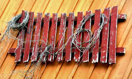 Weathered and worn, red picket fence hangs on wooden wall.  Paint is cracked and frayed rope hangs from boards. 版權商用圖片
