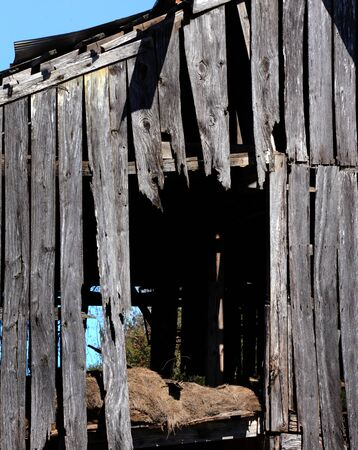 Decaying barn has rustic weathered boards.  Loft has mildewing leftover hay.  Boards are broken and rotting.