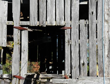 Loft in Derelict Barn is missing its door. Rusty hinges mark where door would have been. Opening is shaped like a block.