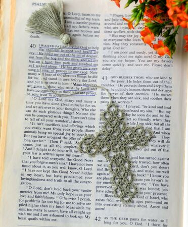 Hand crocheted bookmark lays across the Bible.  Page is opened to comforting words of encouragement.  Fall flowers decorate corner.