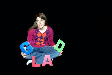 Young woman sits in an all black room holding the letters spelling